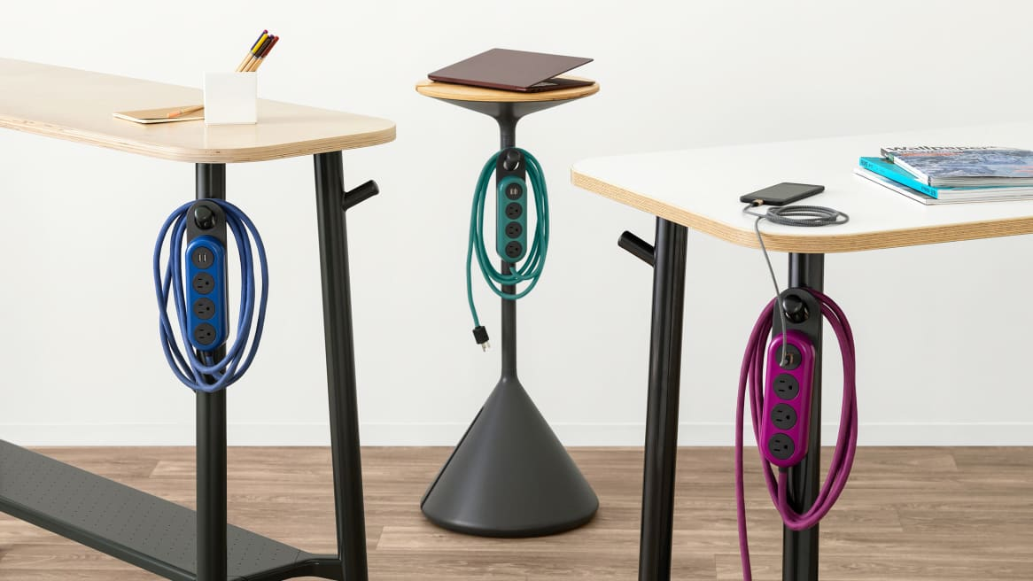 Steelcase Flex Power Hangers in various colors are seen hanging on a Steelcase Flex Stand, Flex Slim Table, and Flex Standing Height table