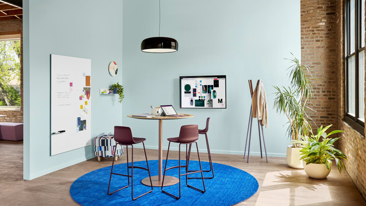Meeting space with Coalesse Enea Lottus stools around a Montara650 table. A Blu Dot Splash coat rack and PolyVision Sans CeramicSteel whiteboard are also seen.