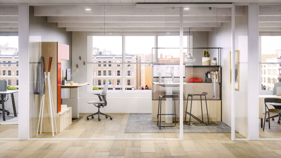 Steelcase Mackinac desk and SILQ chair with another Mackinac worksurface nearby with stools around it