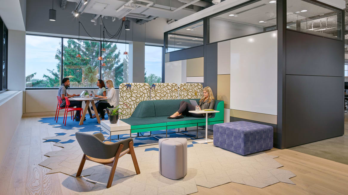 A woman sits on Umami lounge seating with Turnstone Pouf seating and a BFree cube nearby. On the other side of a screen, three people work at a Trestle table while sitting on EMU Lyze chairs.