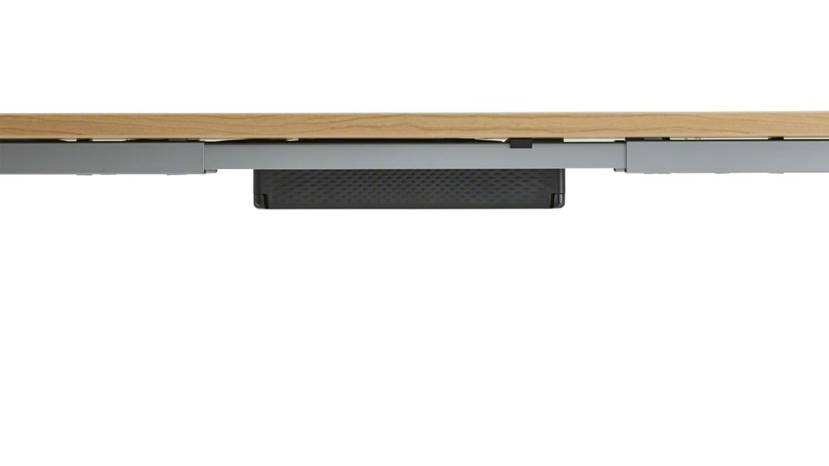 Black Steelcase Universal Cable Management Kit attached into a light wood desk.