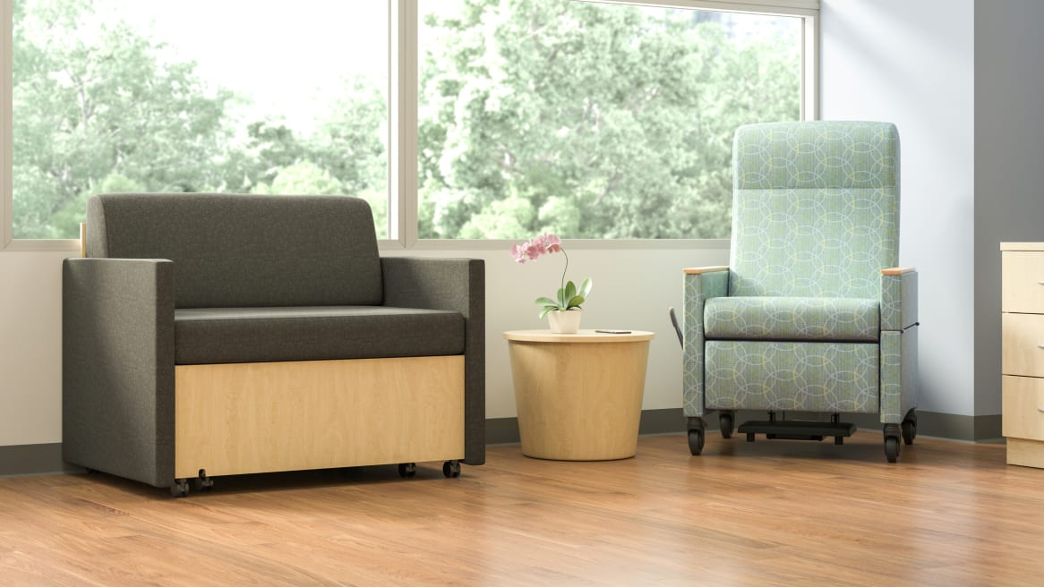 Mineral Patient chair in mint green, next to a brown X-tenz Double Sleeper with a small coffee table in the middle of them.