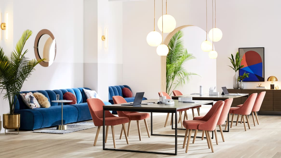 Dining table with four red West Elm Work Sterling Chairs and blue West Elm Work Belle couch