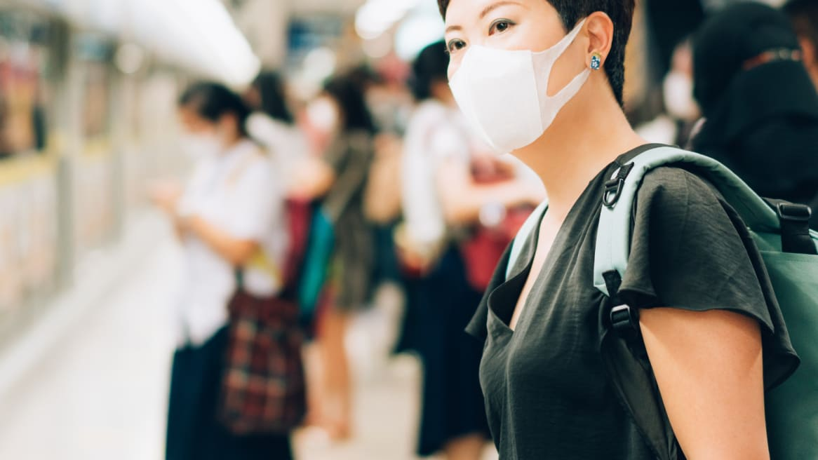 Person wearing a face mask standing at a public transit station