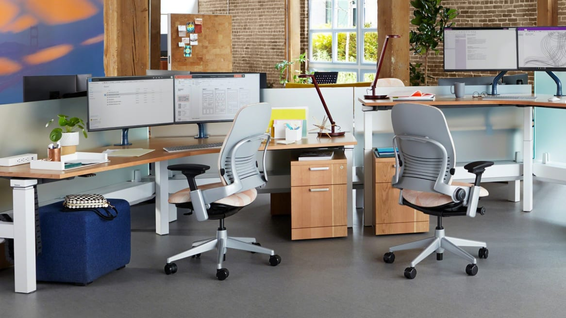 Collaborative space with wooden large desks and storages, two Leaps chairs with pattern on the cushion