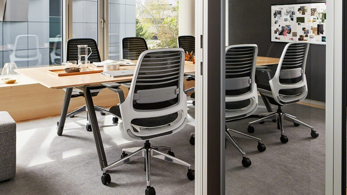 inside a meeting room there is a large wooden table and several black Series 1 chairs