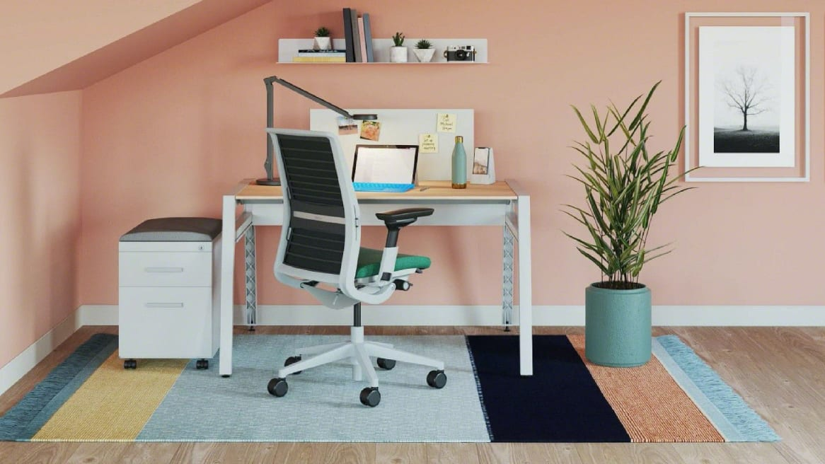 Private home office with a pink wall, wooden desk with a laptop on it, a plant and a blue Think chair