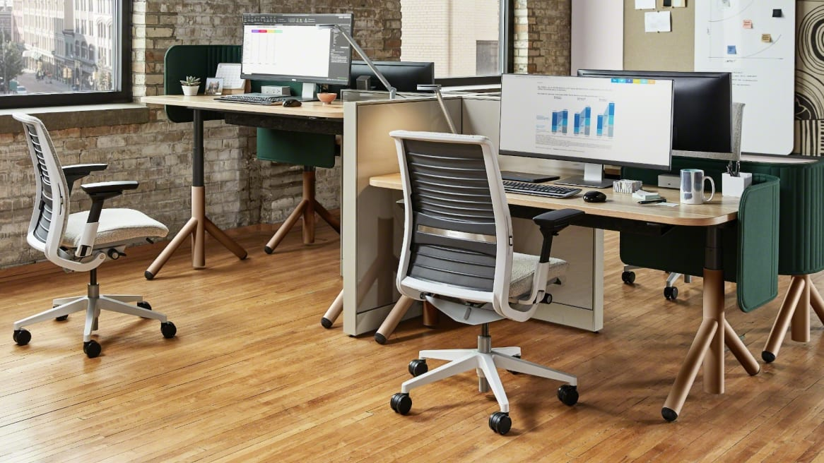 Work area with a wooden desk, a big monitor on it and a Think chair