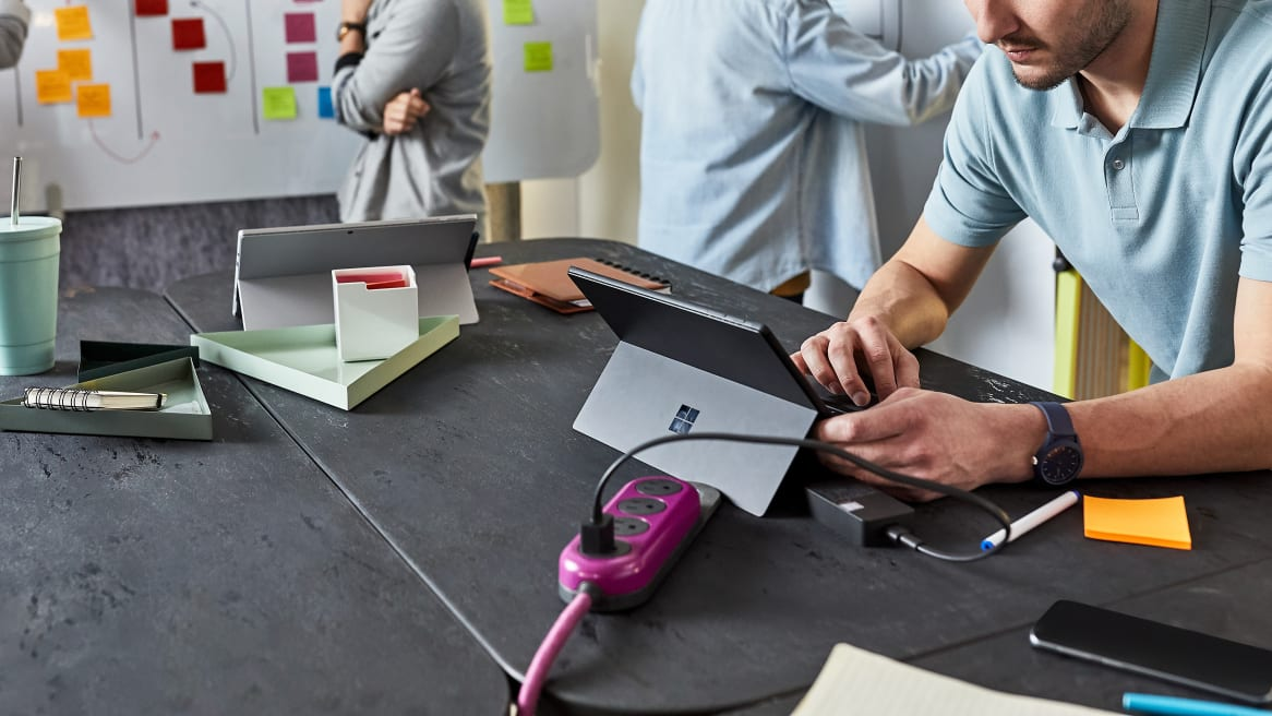 A man charging his tablet on a magenta Steelcase Flex Power Hanger.