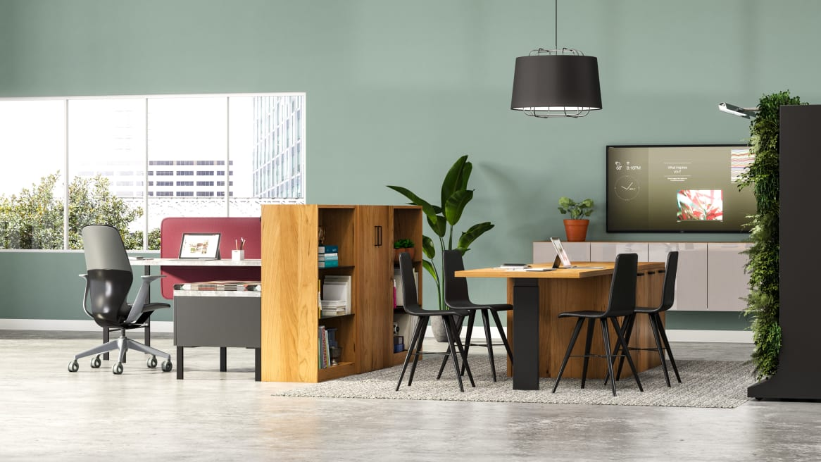 Nomadic Office space equipped with Elective Elements bookcases and storage, gray Bludot rug, black Bolia beaver chair with a TV screen on the back.
