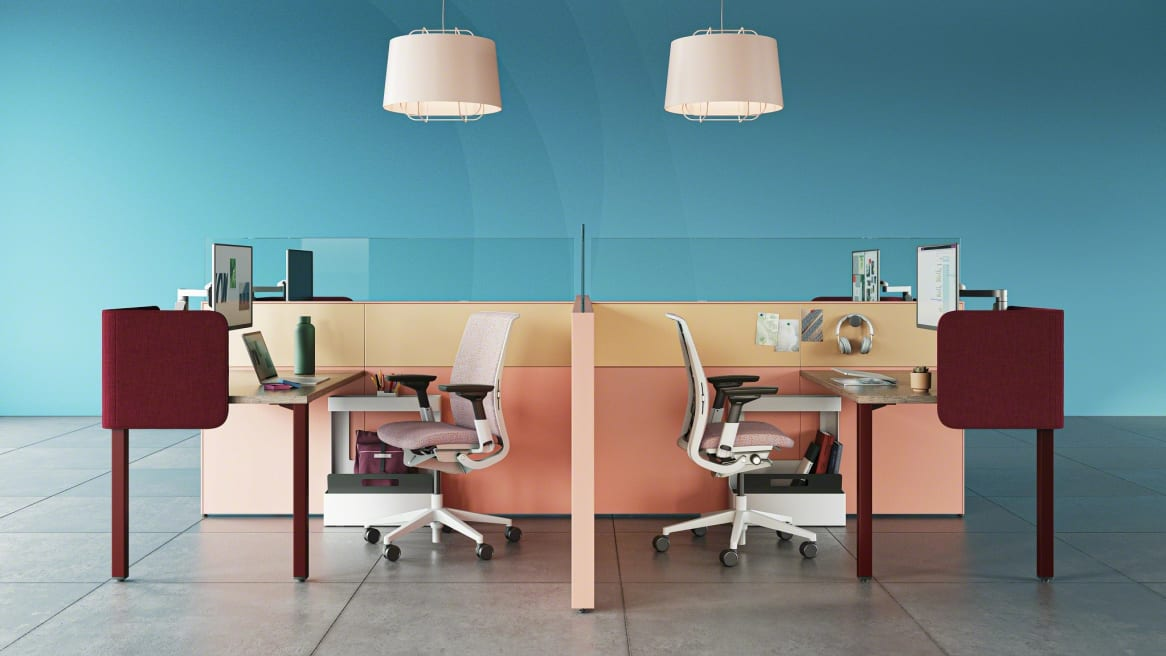 work space divided with pink walls, two rectangular desks and two Gesture chairs, burgundy Sarto screens