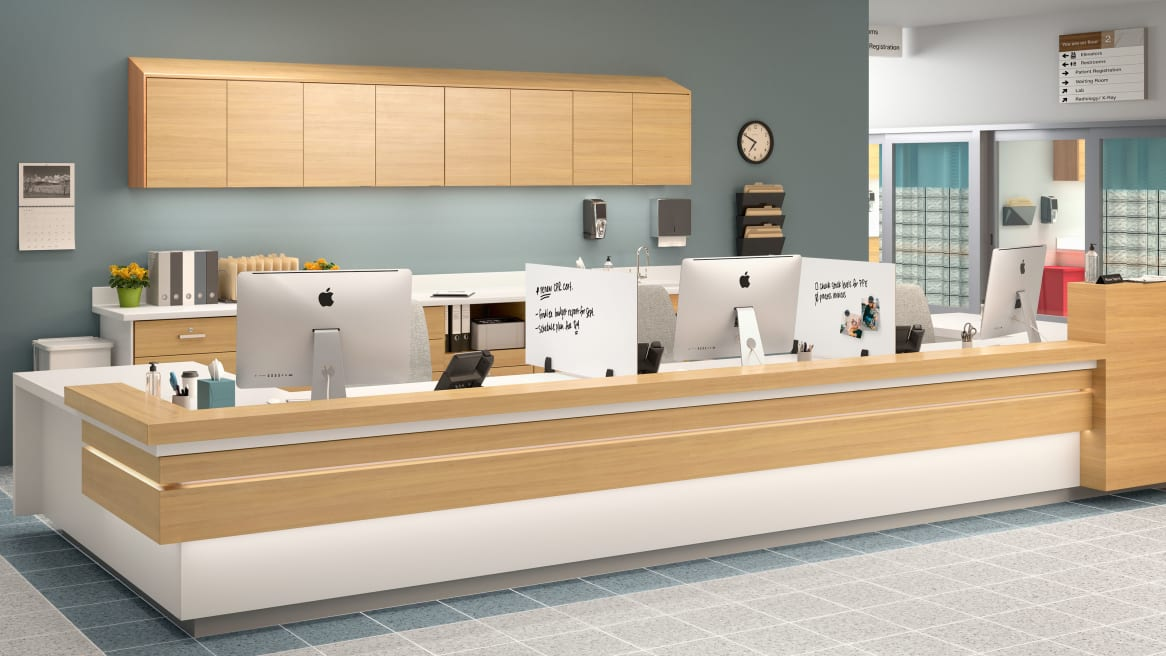 Healthcare reception space equipped with PolyVision Boundri™ screen dividers between the receptionists seats.