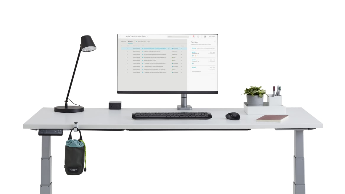 on white image of a desk with a personal light and a monitor