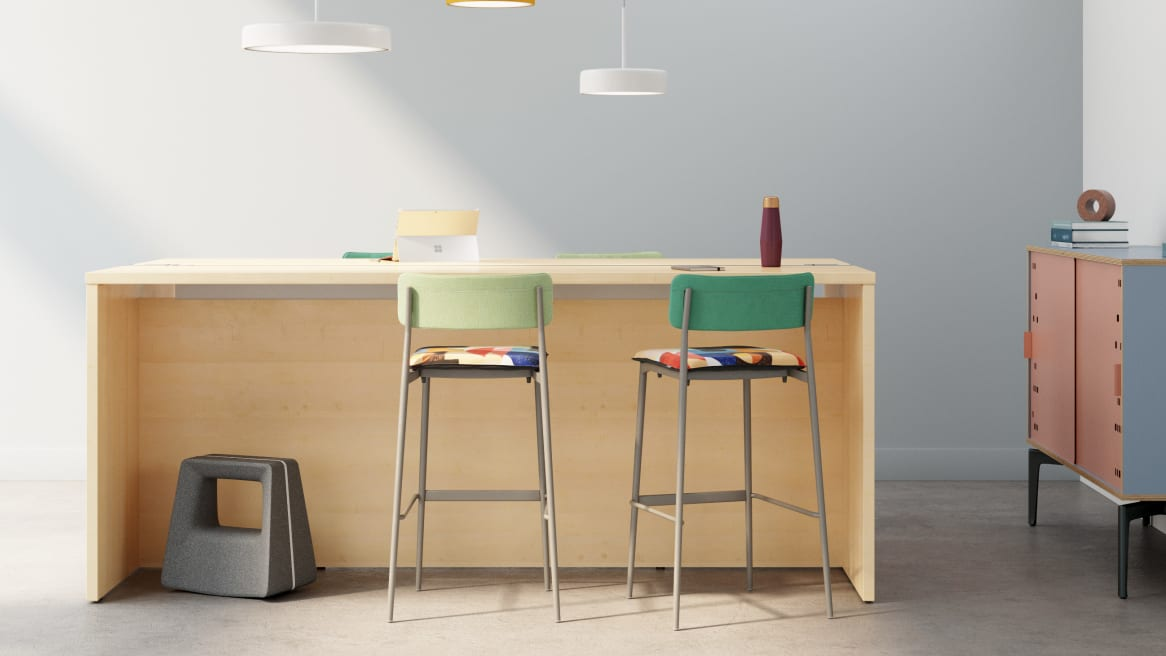 Office space equipped with a high veneer table and green Simple Stools with colorful seats.