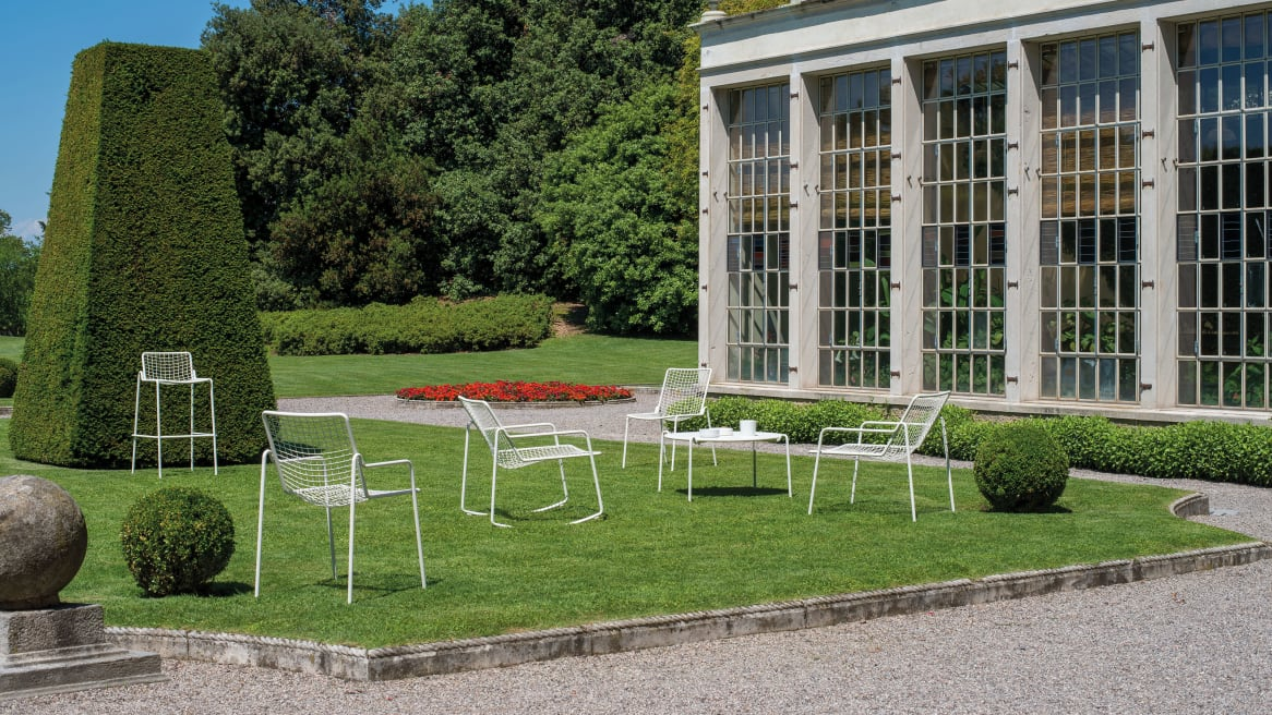 A variety of white EMU Rio R50 Chairs and Stools on a garden.