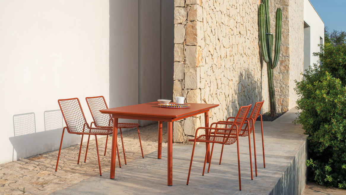 Red EMU Rio R50 Chairs around a red table on an outdoor space.