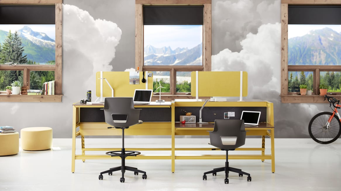 Workstations equipped with yellow Turnstone Bivi Tackable Screens mounted on a yellow Turnstone Bivi Table for Two in front of two gray Steelcase Shortcut stools.