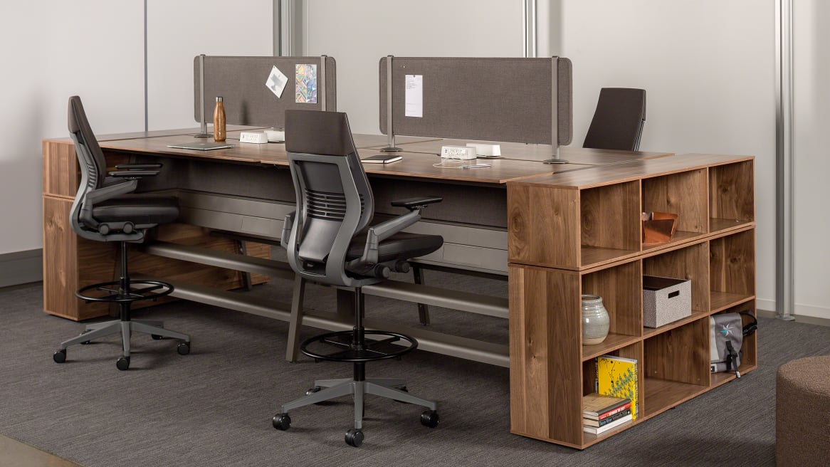 Workstations equipped with gray Turnstone Bivi Tackable Screens mounted on top of a wood Turnstone Bivi Table for Two and black Steelcase Gesture Stools.