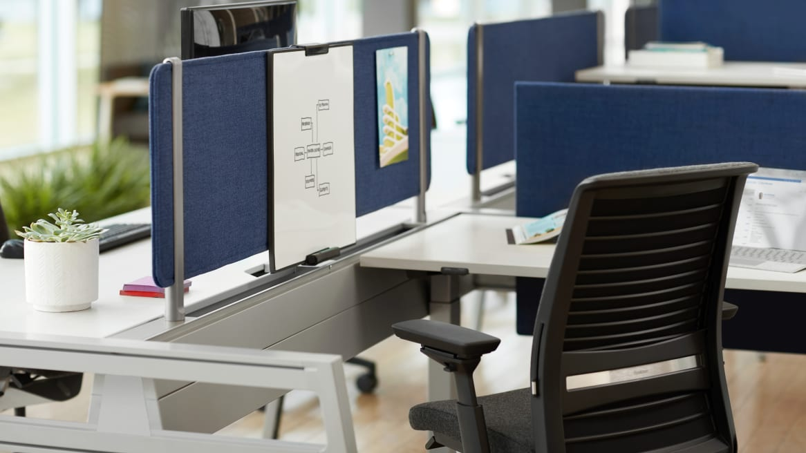 Personal workstation surrounded by blue Turnstone Bivi Tackable Screens with a Turnstone Personal Markerboard and a black Steelcase Think chair.