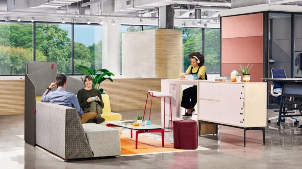 An office lounge with a Campfire Lounge system, Bassline occasional table, Campfire Pouf, Clipper Screen, Campfire Slim standing table, Scoop stools, and Bassline storage