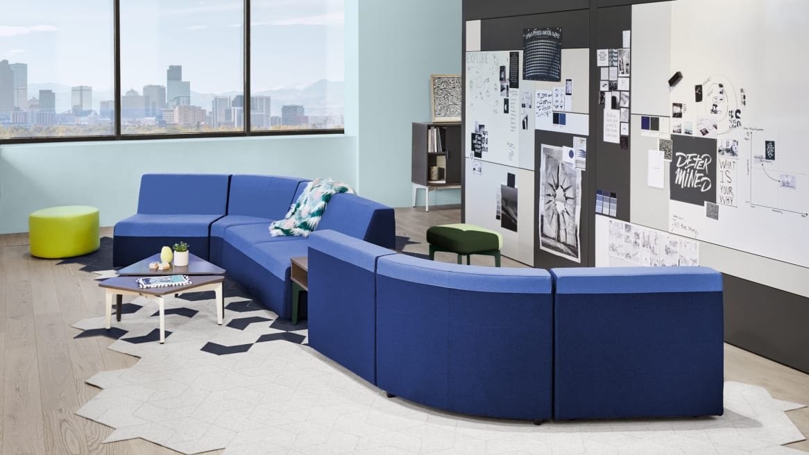 A Campfire Lounge System in blue upholstery in a lounge setting with a Bassline Bench, and Bassline Asymmetrical Tables also pictured