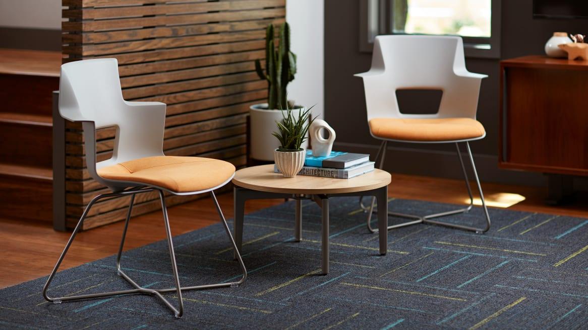 Veneer Turnstone Bassline Occasional Tables in between 2 orange Turnstone Shortcut X Base chairs.