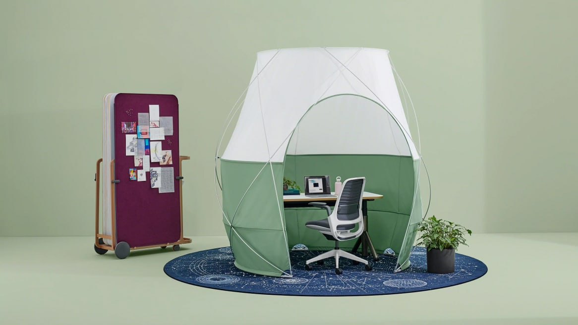Green pod tent with an Amia office chair inside