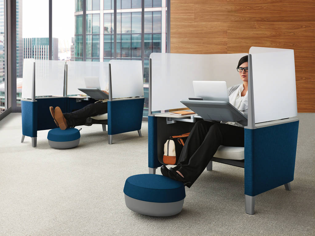 Woman sitting and working on a Brody, Steelcase Product