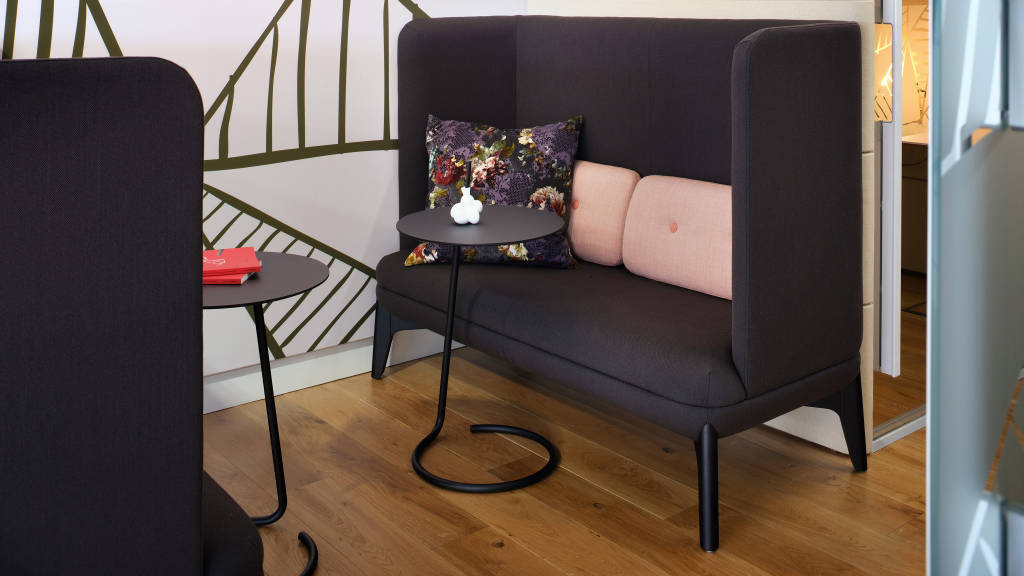Black Orangebox sofa with pink pillows and a personal table in front of it.