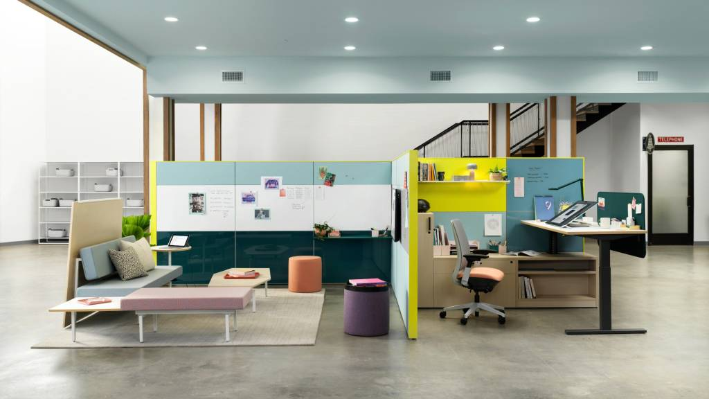 Setting with blue and yellow walls, Adjustable desk, pink office chair, blue sofa.