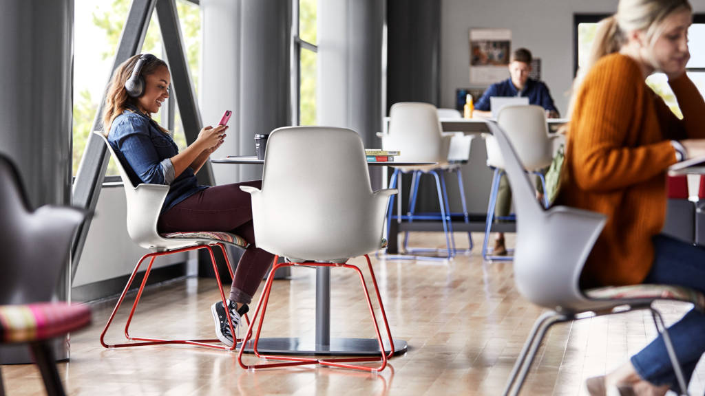 student looking at her cellphone while seated on a Node chair