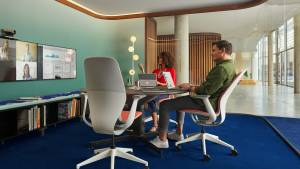 Two people sit in SILQ chairs by Steelcase in a private meeting room while looking at monitors