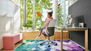 A woman in an office area with a colorful rug sits in a SILQ chair by Steelcase with her back turned toward the camera