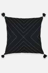 Black pillow with tassels and white stitching by Anchal