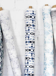 Bolts of fabric with different geometric prints lean against a white brick wall