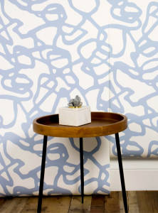 A small round wood table placed next to a wall with a geometric print