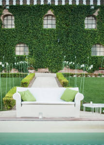 garden with a white Kartell sofa and green pillows