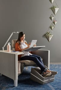 Woman seated on a Brody chair with lamp while using an iPad