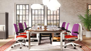 Six Steelcase Series 1 office chairs with red orange seats and purple backs a in meeting room