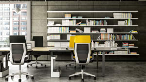Gesture desk chairs with gray and yellow upholstery are arranged around a workstation created using a FrameOne benching system from Steelcase