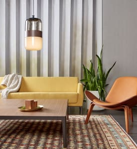 A yellow Visalia three-seat sofa is seen in front of a gray wall and next to a Carl Hansen CH07 Shell Chair with a wood CG_1 square table in front of it