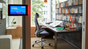A private enclave by a window at LINC offices in Munich includes a Gesture desk chair with headrest and an orange Dash Mini desk lamp from Steelcase